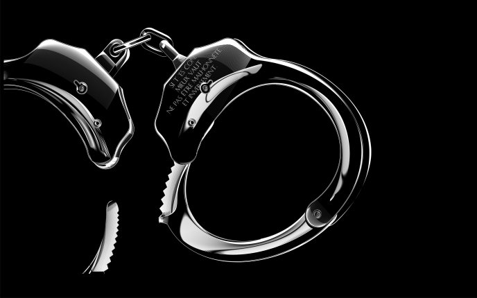 Silver handcuffs on a black wall