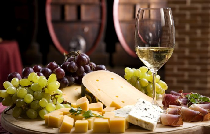 Cheese specialties, prosciutto, grapes and a glass of wine