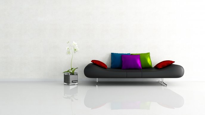 A black sofa with colorful pillows beside a flower