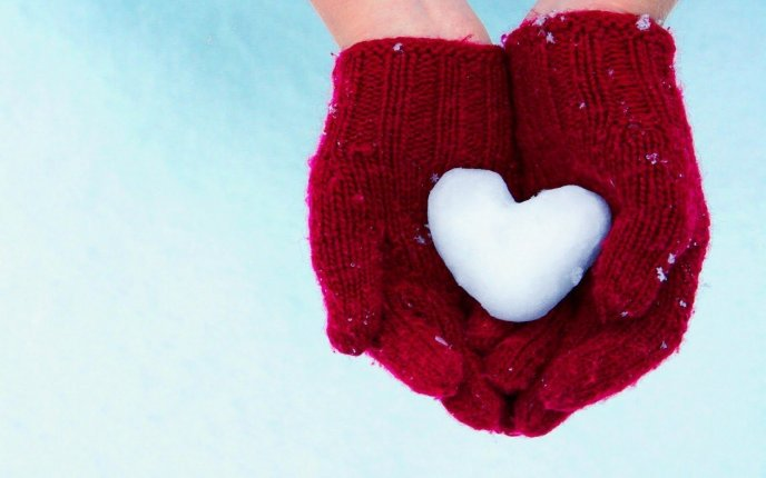Red gloves and a wonderful heart made of snow