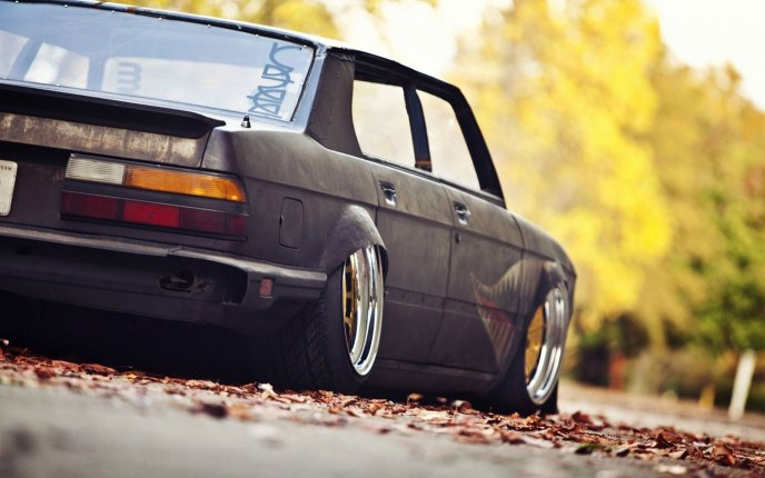 Old Dark Bmw Car And Autumn Leaves On The Road