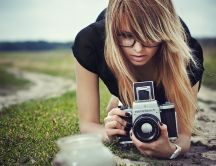 Blonde woman taking photos with a professional camera