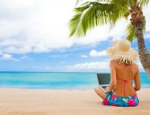 Girl on the beach with her laptop