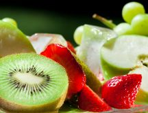 Delicious fruits - kiwi, strawberries, apple and grapes