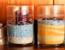 Colored candles in jars with sand