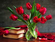 A bouquet of red tulips in a vase next to some books