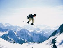 Snowboard jump on the high summits of the mountains