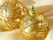 Two golden Christmas ornaments filled with glitter