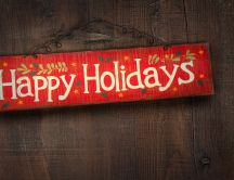 Happy Holidays written on a piece of wood