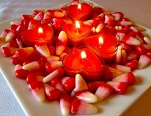 Heart shaped candles and jellies on a plate