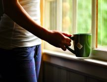 Girl with a green cup of hot tea - good morning sun