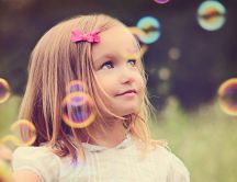 Sweet little blonde girl playing with soap bubbles