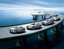 Parade of Toyota cars on the bridge over the ocean