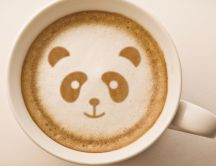 A face of panda bear in a coffee cup