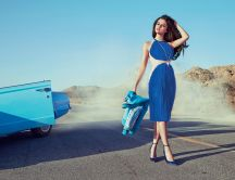 Selena Gomez in blue dress on the road near the blue car