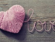 A pink heart made of wool on the wood