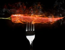A fork with a hot red pepper in flames