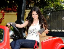 Selena Gomez in a red mini car with her quitar