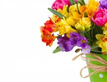 Colorful daffodils and freesias bouquet in a green vase