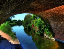 A river under an arched bridge - Nature wallaper