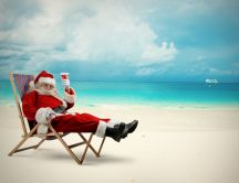 Happy Santa Claus drinking a cocktail on the beach