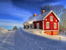 Red house and a beautiful white snow on the road