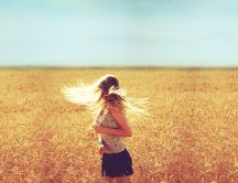 Girl with beautiful blonde hair in the golden wheat field