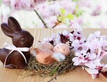 Chocolate Easter bunny and a nest with eggs - Happy Holiday
