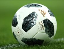 Macro football ball on the green field - Adidas sponsor FIFA
