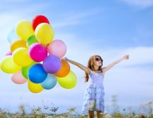 Happy girl with a bouquet of colourful balloons - Childhood