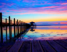 Rainbow colors of sunset over the ocean water and pontoon