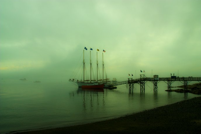 Fog on the sea - boat moored at pier