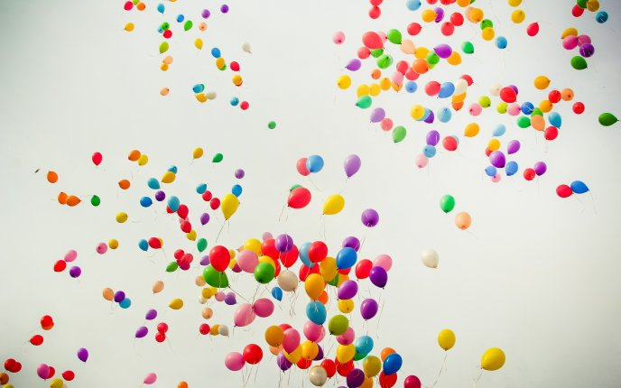 Hundreds of colorful balloons flying through the air