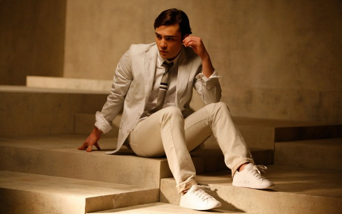 Ed Westwick in a white suit sitting on the stairs