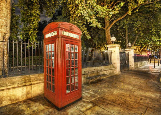 Red telephone booth on the sidewalk in London HD wallpaper