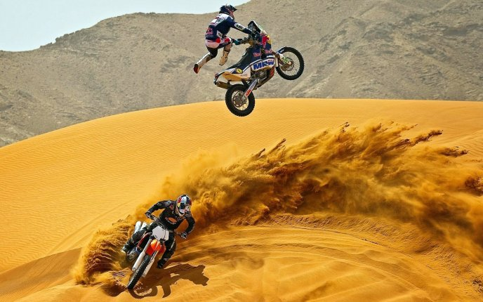 Motorcycle jumping contest on sand dunes