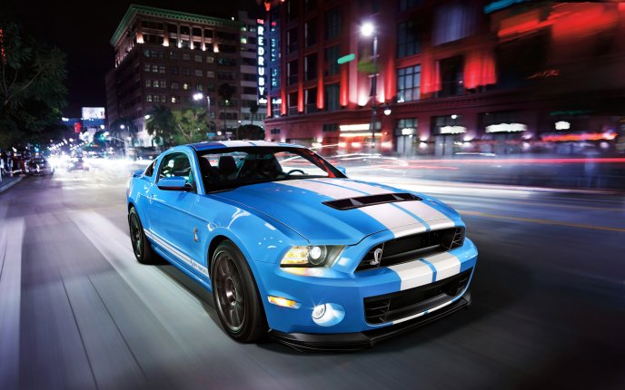 Shiny blue Mustang Shelby GT500 run in the city