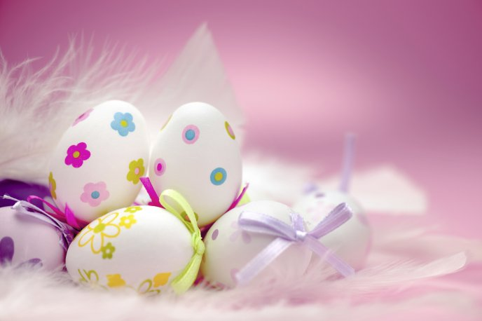 White eggs with beautiful drawings on the pink background