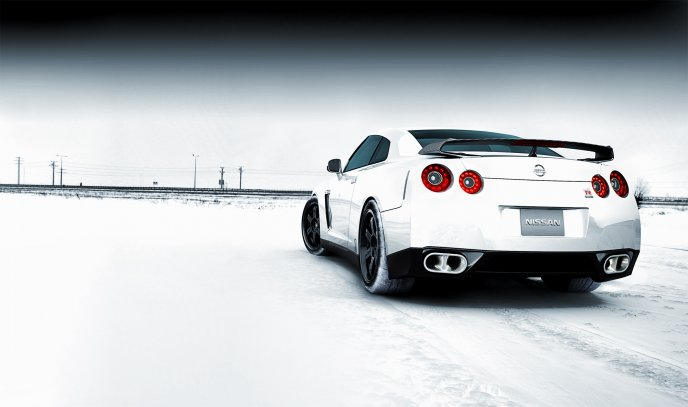 White Nissan car on the road full with snow