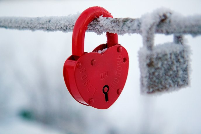 Red lock on a frozen bar - Cold winter season
