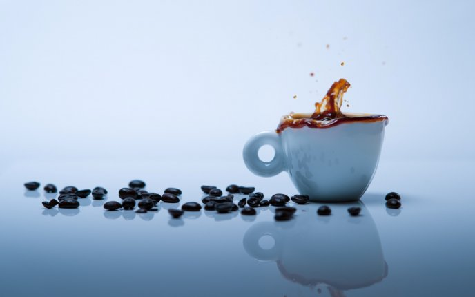 Coffee beans splash in a white cup full with coffee