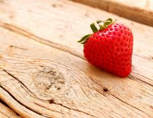 A delicious strawberry on a piece of wood