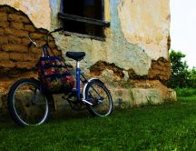 Bike leaning against an old house of clay