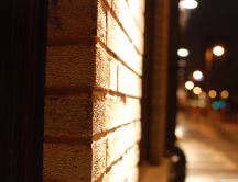Brick wall close up - blurry street at night