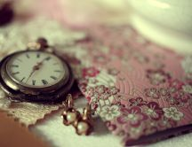 Old pocket clock, earrings and pink envelope on the table