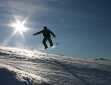 Snowboard jumping in sunlight HD wallpaper