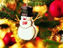 Christmas ornament shaped snowman hanging in the tree