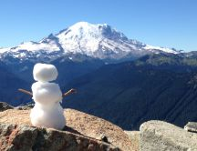 Little snowman on the top of the mountain