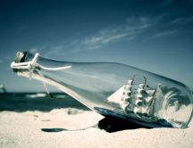 A ship in a bottle on the hot sand HD wallpaper