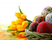 Hand painted eggs in front and yellow tulips